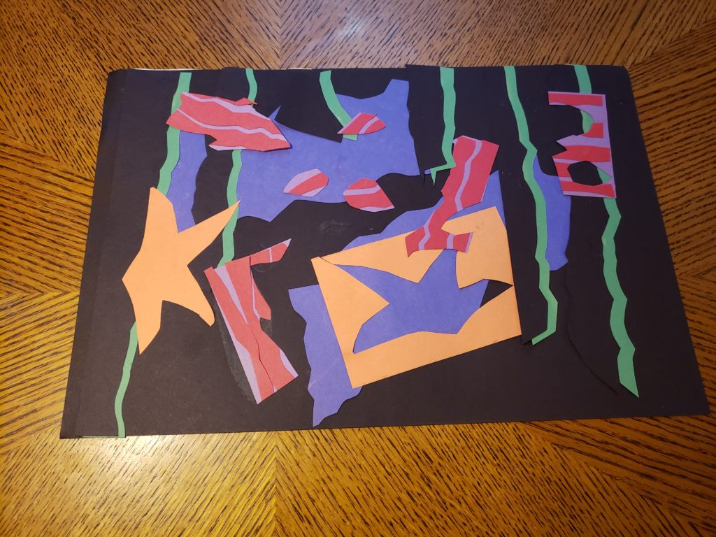 An abstract paper collage of undersea life. Two parallel fluffy blue rectangles are hidden behind many other shapes. Narrow black strips with green shadows and varying heights are placed evenly across the page. An orange starfish and an orange rectangle with a starfish cut out of it are placed with many red and purple striped, jagged shapes  on top of the black strips.
