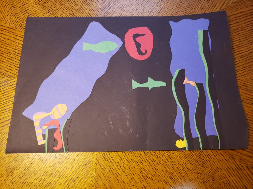 An abstract paper collage of undersea life; two fluffy blue rectangles are set in a black background, the left rectangle diagonal while the right is standing straight. Three narrow, black strips with green shadows stand in front of the right rectangle while two short strips stand in front of the left. Several green fish shapes and several red or yellow and purple striped seahorse shapes swim around. A circular shape with a seahorse cut out of its center floats near the upper center of the page.