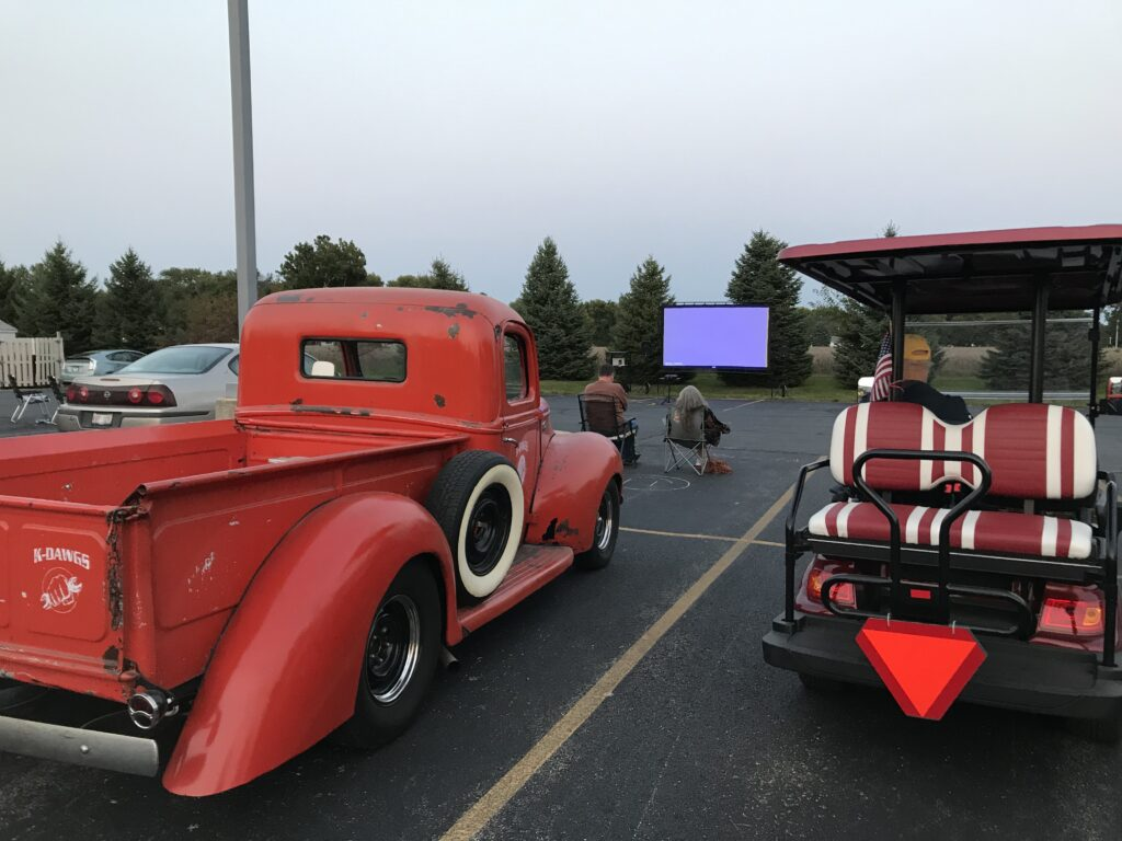 Red truck and red golf cart parked at a drive in movie at dusk.