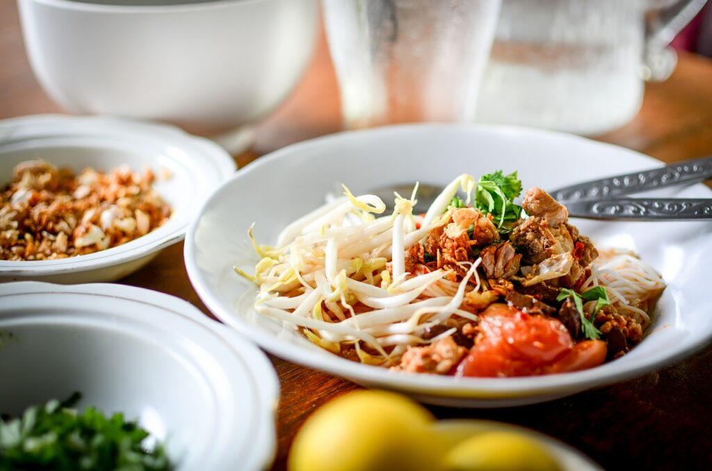 Shallow white bowl with colorful food and bean sprouts